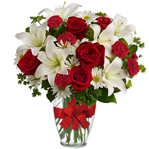 Classic red roses, miniature carnations, daisy spray chrysanthemums and majestic white Asiatic lilies are arranged in a clear glass vase. This beautiful and sumptuous arrangement is perfect for all special occasions and an ideal gift for a sweetheart.