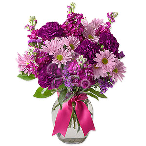 A magical and luxurious purple extravaganza of mauve daisy poms, purple toned carnations, amethyst statice, tightly clustered and set off by fresh green salal.