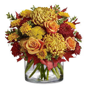 Chrysanthemums in shades of bronze, rust and yellow, cast evening rays over orange roses and yarrow rising from a lush bed of greens reclining in a clear vase, making it a perfect gift this season.