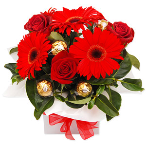 A bright red arrangement with irresistable chocolates wired between the blooms. A lovely, romantic gesture.
