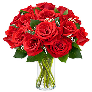 An alluring composition of style and luxury highlighting a natural beauty is presented through this extravagant collection of a dozen red roses arranged delicately with green fillers in a glass vase.